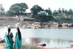Två indiska kvinnor ser staden på floden med deras baksidor till kameran på sjön royaltyfria bilder