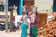 Två indiska kvinnor som bär tegelstenar på deras huvud Två kvinnor fotograferas från baksidan Royaltyfri Fotografi