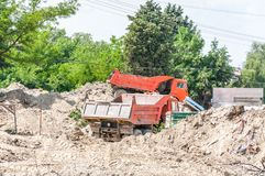 Två industriella person som ger drickslastbilar på jord- eller jordningsutgrävningplatsen som är klar att laddas royaltyfri fotografi