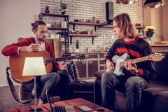 Två instrumentalister som sitter i köket och har repetition arkivfoton