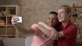 Två internationella glade vänner och att sitta på soffan och att krama och att göra selfies som skrattar Homeliness romantisk aft lager videofilmer