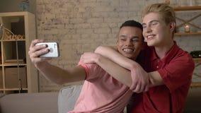 Två internationella glade vänner och att sitta på soffan och att krama och att göra selfies som skrattar Homeliness romantisk aft arkivfilmer