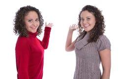 Två isolerade flickor som framlägger över den vita bakgrundsdanandepromoen Arkivbilder