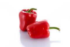 Två isolerade röda peppar Arkivbild