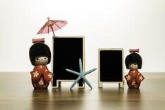 Två japanska dockor med det svarta brädet för två mellanrum med fisken för blå stjärna och det röda paraplyet Royaltyfri Bild