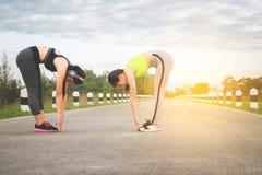 Två joggar attraktiv kvinnlig på löparbanan, sträckning som kör, royaltyfri fotografi