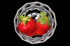 Två jordgubbar i ett exponeringsglas som isoleras royaltyfria bilder