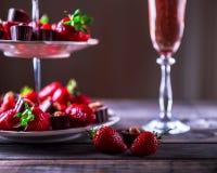 Två jordgubbar på en trätabell Ställning med jordgubbar och Royaltyfria Bilder