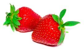 Två jordgubbar stänger sig upp på vit bakgrund royaltyfria bilder