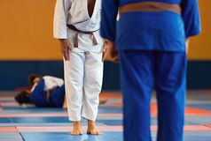 Tv? judok?mpar eller idrottsman nen som h?lsar sig i en pilb?ge, innan ?vning av kampsporter arkivfoton
