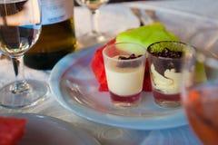 Två kakor på en platta med ett exponeringsglas av vin och frukt royaltyfria bilder