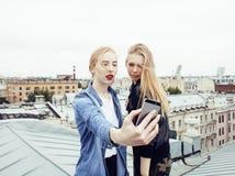 Två kalla blonda verkliga flickavänner som gör selfie på taköverkanten, livsstilfolkbegrepp, modern tonår Arkivfoton