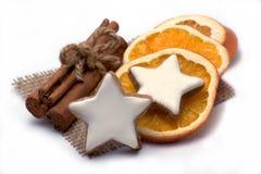 Två kanelbruna stjärnor med orange skivor och kanel Arkivbilder