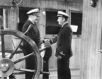 Två kaptener som skakar händer på ett fartyg (alla visade personer inte är längre uppehälle, och inget gods finns Leverantörgaran arkivbild