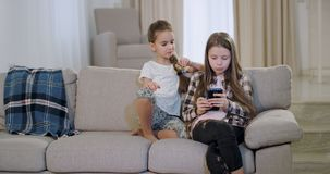 Två karismatiska systrar som sitter på soffan och äter några kex och spelar på en smartphone som spenderar en rolig tid stock video