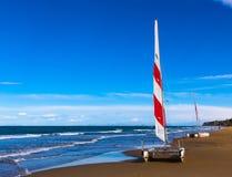 Två katamaran med rött och vitt seglar och att stå på strandsanden arkivbild