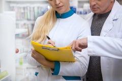 Två kemister som tillsammans arbetar på apoteket royaltyfria bilder