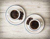 Två keramiska koppar kaffe på träbakgrunden Arkivbild