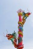 Två kinesiska drakar som slås in runt om röd pol Arkivbilder