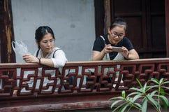Två kinesiska turister i Yuyuan trädgårdar i Shaghai, Kina Royaltyfri Fotografi