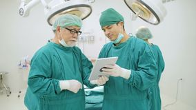 Två kirurger som läser en tålmodig ` s, case historia i operationrum stock video