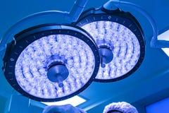 Två kirurgiska lampor i tagande för operationrum med blått filtrerar royaltyfri fotografi