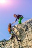 Två klättrare som når den hållande handen för toppmöte en av Royaltyfri Fotografi