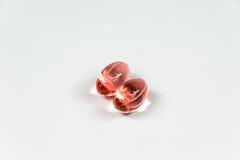Två klara röda mjuka gelatinkapslar Fotografering för Bildbyråer