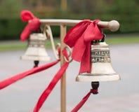 Två klockor med det röda bandet på ställningen för brudgummen och bruden Arkivbilder