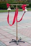 Två klockor med det röda bandet på ställningen för brudgummen och bruden Arkivfoto
