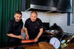 Två kockar på arbete i en restaurang Kock kock, jobb arkivbild