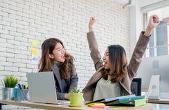 Två kollegaaffärskvinnaarmar upp för goda nyheter från jobb på la royaltyfri bild