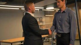 Två kollegor som inom skakar händer av det moderna affärskontoret arkivfilmer