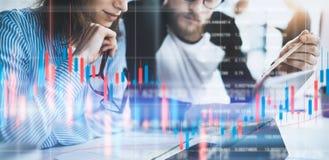 Två kollegor som sitter den främre bärbar datordatoren med finansiell grafer och statistik på bildskärm dubbel exponering arkivfoton