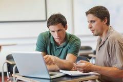 Två koncentrerade stiliga mogna studenter som sitter i grupp arkivbild