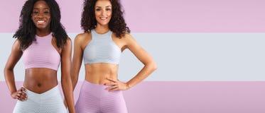 Två konditionkvinnor i sportswearen som isoleras över grå bakgrund Chopy utrymme för sport- och modebegreppsintelligens arkivfoton