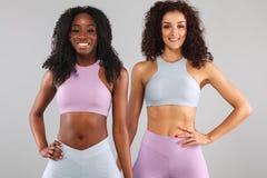 Två konditionkvinnor i sportswearen som isoleras över grå bakgrund Sport- och modebegrepp med kopieringsutrymme royaltyfria foton