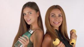 Två konditionkvinnor som ler på de och att posera med vattenflaskan och hantlar arkivbilder
