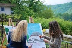 Två konstnärflickor målar byggnaden i natur arkivbilder