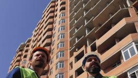 Två konstruktionschefer i hjälmar med ett skägg och en mustasch att diskutera konstruktionsdetaljer på konstruktionsplatsen 4K lager videofilmer