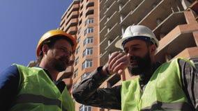 Två konstruktionschefer i hjälmar med ett skägg och en mustasch att diskutera konstruktionsdetaljer på konstruktionsplatsen 4K arkivfilmer