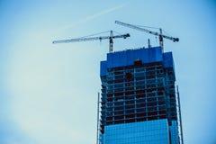Två konstruktionskranar bygger en skyskrapa arkivbilder