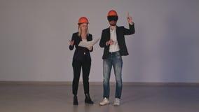 Två konstruktionsteknikerer i hjälmar med VR rullar med ögonen klara av byggnadsprojekt i 3d Royaltyfria Foton