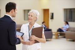 Två konsulenter som diskuterar patientanmärkningar i sjukhus royaltyfria foton