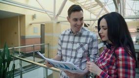 Två kontorsarbetare diskuterar statistikdokument inom arkivfilmer
