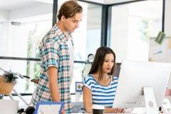 Två kontorsarbetare på skrivbordet Fotografering för Bildbyråer