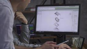 Två kontorsarbetare sitter framme av datoren och diskuterar teckningen för byggnads` s, övertid, bitultrarapid stock video