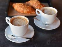 Två kopp kaffe med nytt bakade giffel royaltyfria bilder