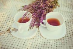 Två kopp te på en pläd med buketten av ljung Arkivbild