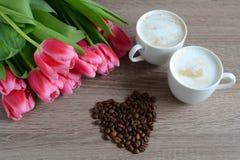 Två koppar av cappuccino med blommor Arkivbild
